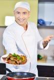 Πιάτο εκμετάλλευσης μαγείρων με τα τρόφιμα στο χαιρετισμό της χειρονομίας Στοκ εικόνες με δικαίωμα ελεύθερης χρήσης