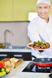 Πιάτο εκμετάλλευσης μαγείρων με τα τρόφιμα στο χαιρετισμό της χειρονομίας Στοκ φωτογραφία με δικαίωμα ελεύθερης χρήσης