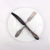 Πιάτο δικράνων, μαχαιριών και γευμάτων στο λευκό Στοκ Φωτογραφία