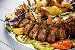 Πιάτο κρέατος με τα εύγευστα κομμάτια του κρέατος, της σαλάτας, των πλευρών, των ψημένων στη σχάρα λαχανικών και των πατατών στον Στοκ φωτογραφίες με δικαίωμα ελεύθερης χρήσης