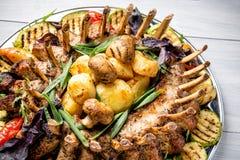 Πιάτο κρέατος με τα εύγευστα κομμάτια του κρέατος, της σαλάτας, των πλευρών, των ψημένων στη σχάρα λαχανικών και των πατατών στον Στοκ φωτογραφία με δικαίωμα ελεύθερης χρήσης
