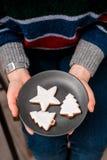 Πιάτο λαβής χεριών γυναίκας με τα μπισκότα Χριστουγέννων στοκ εικόνες με δικαίωμα ελεύθερης χρήσης