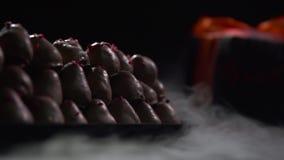 Πιάτο με τα μούρα στη σοκολάτα σε ένα υπόβαθρο με ένα κιβώτιο με ένα τόξο απόθεμα βίντεο