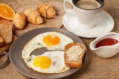 Πιάτο με τα τηγανισμένα αυγά και φρυγανιά με το βούτυρο, croissants, ψωμί ο Στοκ εικόνες με δικαίωμα ελεύθερης χρήσης
