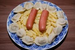 Πιάτο με τα τρόφιμα, λουκάνικα, μπουλέττες, ζυμαρικά Στοκ Εικόνες