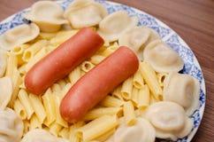 Πιάτο με τα τρόφιμα, λουκάνικα, μπουλέττες, ζυμαρικά Στοκ εικόνα με δικαίωμα ελεύθερης χρήσης
