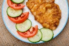 Πιάτο με την τηγανισμένη μπριζόλα κρέατος στο κτύπημα αυγών και την τεμαχισμένη ντομάτα και το γ Στοκ Φωτογραφία