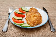 Πιάτο με την τηγανισμένη μπριζόλα κρέατος στο κτύπημα αυγών και την τεμαχισμένη ντομάτα και το γ Στοκ εικόνες με δικαίωμα ελεύθερης χρήσης