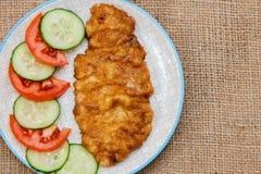 Πιάτο με την τηγανισμένη μπριζόλα κρέατος στο κτύπημα αυγών και την τεμαχισμένη ντομάτα και το γ Στοκ Εικόνες