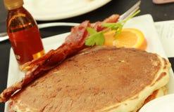 Πιάτο με τις νόστιμες τηγανίτες και μπέϊκον στον πίνακα στοκ εικόνα