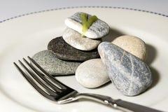 Πιάτο με τις πέτρες και ένα δίκρανο Στοκ Φωτογραφίες
