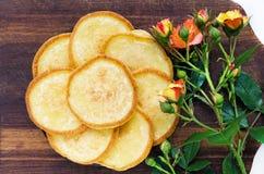 Πιάτο με τις τηγανίτες σε έναν καφετή ξύλινο πίνακα με ένα ροδαλό λουλούδι Στοκ εικόνα με δικαίωμα ελεύθερης χρήσης