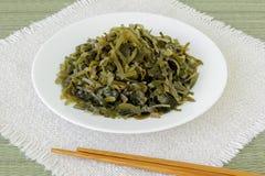 Πιάτο με τις φέτες παστωμένα kelp και chopsticks σε μια πλαισιωμένη επιτραπέζια πετσέτα Το εδώδιμο φύκι περιέχει πολύ ιώδιο και στοκ εικόνες