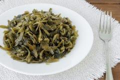 Πιάτο με τις φέτες παστωμένο kelp και ενός δικράνου σε μια πλαισιωμένη επιτραπέζια πετσέτα Το εδώδιμο φύκι περιέχει πολλά ιώδιο κ στοκ εικόνες με δικαίωμα ελεύθερης χρήσης