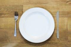 Πιάτο με το δίκρανο και μαχαίρι με το ξύλινο υπόβαθρο Στοκ εικόνες με δικαίωμα ελεύθερης χρήσης