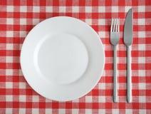 Πιάτο με το δίκρανο και μαχαίρι σε ένα κόκκινο ελεγμένο τραπεζομάντιλο Στοκ Φωτογραφία
