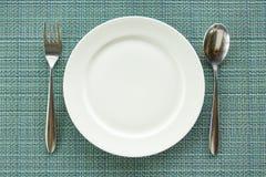 Πιάτο με το κουτάλι και δίκρανο στον πίνακα Στοκ εικόνα με δικαίωμα ελεύθερης χρήσης