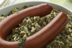 Πιάτο με το μαγειρευμένα σγουρό κατσαρό λάχανο και το λουκάνικο Στοκ Εικόνα