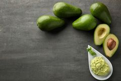 Πιάτο με το νόστιμο guacamole και ώριμα αβοκάντο στον πίνακα στοκ εικόνες