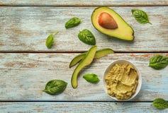 Πιάτο με το νόστιμο guacamole και ώριμο αβοκάντο στον ξύλινο πίνακα στοκ εικόνες