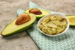 Πιάτο με το νόστιμο guacamole και ώριμο αβοκάντο στον πίνακα στοκ φωτογραφία
