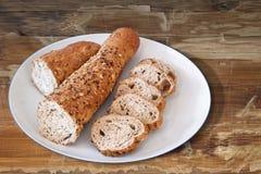 Πιάτο πορσελάνης το ακέραιο καφετί ψωμί Baguette που κόβεται με στις φέτες Στοκ εικόνα με δικαίωμα ελεύθερης χρήσης