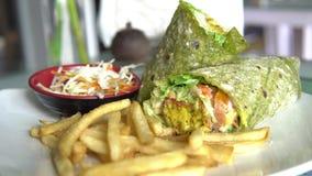 Πιάτο που εξυπηρετείται με ένα περικάλυμμα falafel, μια φυτική σαλάτα, και τις τηγανιτές πατάτες απόθεμα βίντεο