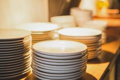 Πιάτο που συσσωρεύεται άσπρο στον πίνακα στο φως βολφραμίου στοκ εικόνες