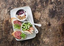 Πιάτο προγευμάτων ή πρόχειρων φαγητών - το σαλάμι, τυρί κρέμας, μικροϋπολογιστής πρασινίζει το bruschetta, τα μήλα, το ακτινίδιο, Στοκ φωτογραφία με δικαίωμα ελεύθερης χρήσης
