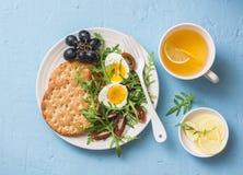 Πιάτο προγευμάτων - η κροτίδα, arugula, ντομάτες κερασιών, έβρασε τη σαλάτα αυγών και το πράσινο τσάι με το λεμόνι στο μπλε υπόβα Στοκ Φωτογραφίες