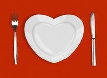 Πιάτο στη μορφή της καρδιάς, του επιτραπέζιου μαχαιριού και του δικράνου Στοκ εικόνα με δικαίωμα ελεύθερης χρήσης