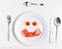 Πιάτο τα αστεία emoticons που γίνονται με από τα τρόφιμα με τα μαχαιροπήρουνα στο λευκό Στοκ εικόνες με δικαίωμα ελεύθερης χρήσης