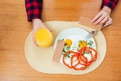 Πιάτο τα τηγανισμένα αυγά που τρώονται με από τη γυναίκα για το πρόγευμα Στοκ Εικόνα