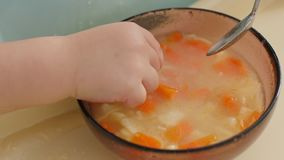 Πιάτο της φυτικής σούπας στην οποία το χέρι του παιδιού βάζει φιλμ μικρού μήκους