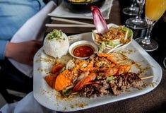 Πιάτο του βόειου κρέατος τριών οβελιδίων, των γαρίδων και του κοτόπουλου όλα που μαρινάρονται στη σάλτσα σχαρών που εξυπηρετείται Στοκ φωτογραφία με δικαίωμα ελεύθερης χρήσης
