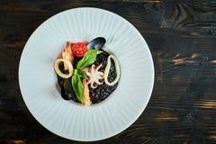 Πιάτο του risotto με το μελάνι καλαμαριών στο γκρίζο πιάτο jpg Στοκ Φωτογραφίες