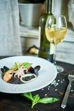 Πιάτο του risotto με το μελάνι καλαμαριών στο γκρίζο πιάτο jpg Στοκ Εικόνες