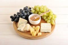 Πιάτο τυριών - διάφοροι τύποι τυριών, σταφύλια πράσινα και μαύρα, στοκ εικόνα με δικαίωμα ελεύθερης χρήσης