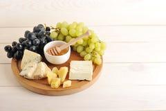 Πιάτο τυριών - διάφοροι τύποι τυριών, σταφύλια πράσινα και μαύρα, στοκ εικόνες με δικαίωμα ελεύθερης χρήσης