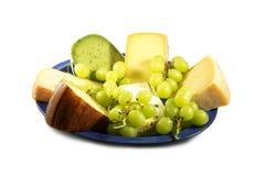 Πιάτο τυριών, διαφορετικοί τύποι τυριών και σταφύλια σε ένα μπλε pla στοκ φωτογραφία με δικαίωμα ελεύθερης χρήσης