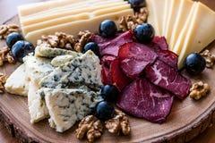 Πιάτο τυριών με το καπνισμένα κρέας, τα ξύλα καρυδιάς και τα σταφύλια στην ξύλινη επιφάνεια στοκ εικόνες