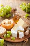 Πιάτο τυριών με camembert, το τυρί Cheddar, τα σταφύλια και το μέλι Στοκ εικόνα με δικαίωμα ελεύθερης χρήσης
