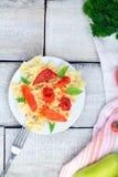 Πιάτο των ζυμαρικών με τη σάλτσα ντοματών με τα συστατικά για το μαγείρεμα στο άσπρο ξύλινο υπόβαθρο, τοπ άποψη με το διάστημα αν Στοκ Εικόνες