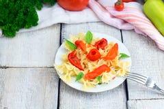Πιάτο των ζυμαρικών με τη σάλτσα ντοματών με τα συστατικά για το μαγείρεμα στο άσπρο ξύλινο υπόβαθρο, τοπ άποψη με το διάστημα αν Στοκ εικόνες με δικαίωμα ελεύθερης χρήσης