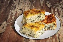Πιάτο των σερβικών φετών Zeljanica πιτών σπανακιού τυριών που τίθενται στην παλαιά ξύλινη επιτραπέζια επιφάνεια Στοκ φωτογραφίες με δικαίωμα ελεύθερης χρήσης
