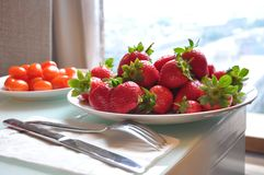 Πιάτο των φρέσκων φραουλών και των ντοματών κερασιών στον πίνακα κοντά στο παράθυρο στοκ φωτογραφίες