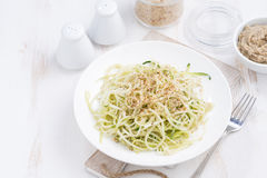 πιάτο των χορτοφάγων ζυμαρικών με τα κολοκύθια και τα καρύδια στον άσπρο πίνακα Στοκ Φωτογραφίες