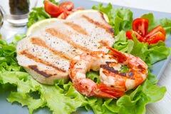 Πιάτο των ψημένων στη σχάρα ψαριών με τις ντομάτες σαλάτας και κερασιών Στοκ Εικόνα