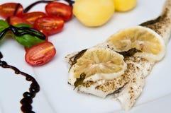 Πιάτο ψαριών βακαλάων με τα λεμόνια και τις ντομάτες Στοκ Φωτογραφίες