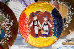 Πιάτο όπου το υπόβαθρο της μολδαβικής σημαίας, το αγόρι και το κορίτσι αντέχουν με το καλάθι των λουλουδιών Στοκ Φωτογραφίες
